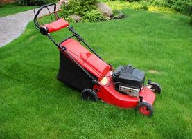 Image of a red lawnmower on grass